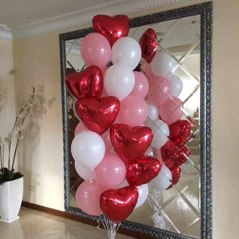 Композиция из бело-розовых шаров с красными сердцами